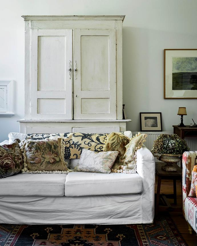 "A timber armoire stores vintage crockery and linen in the living room. The white slip-covered sofa is from IKEA. The interior of the house was originally more colourful — a mix of Victorian pinks and greens. The Thumpstons painted the walls [Dulux](https://www.dulux.com.au/|target=""_blank""
