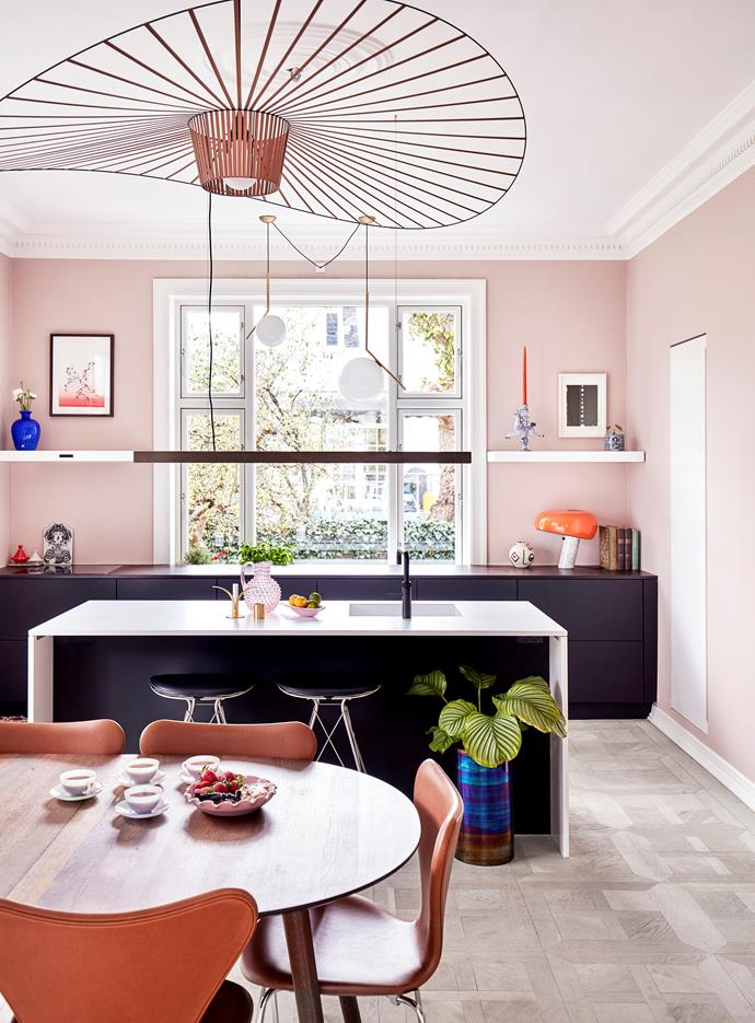 The Unoform kitchen offers a wealth of colour contrasts, from the marine blue Murano vase against the pink walls, to the classic combination of black and white work surfaces. The black low-hanging lamp over the island is from Anour.