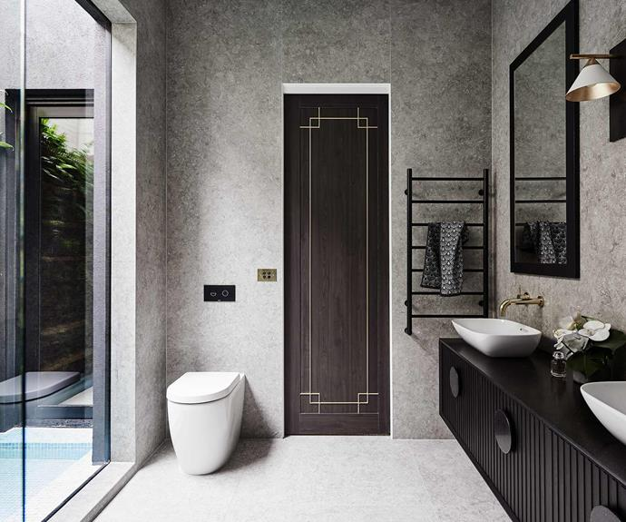 **Bathroom** A stunning Zuster cabinet anchors the bathroom and complements black fixtures that pop against the mottled grey tiles.
