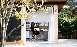 Woman in a home office that opens onto a deck