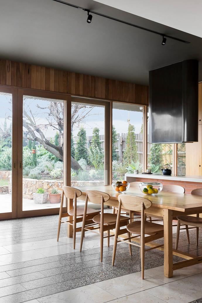 Terrazzo floor tiles run throughout the open plan dining room, which is the homeowner's favourite room in the house. Sliding doors allow the space to spill out into the terrace garden. The dining table is a repurposed tailor's bench.