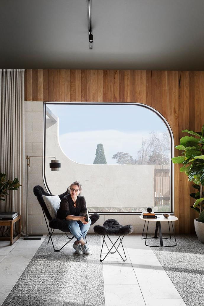 Homeowner Elizabeth Wilmott sits in a fur-covered butterfly chair in front of a curved double-glazed feature window, made from Viridian glass.