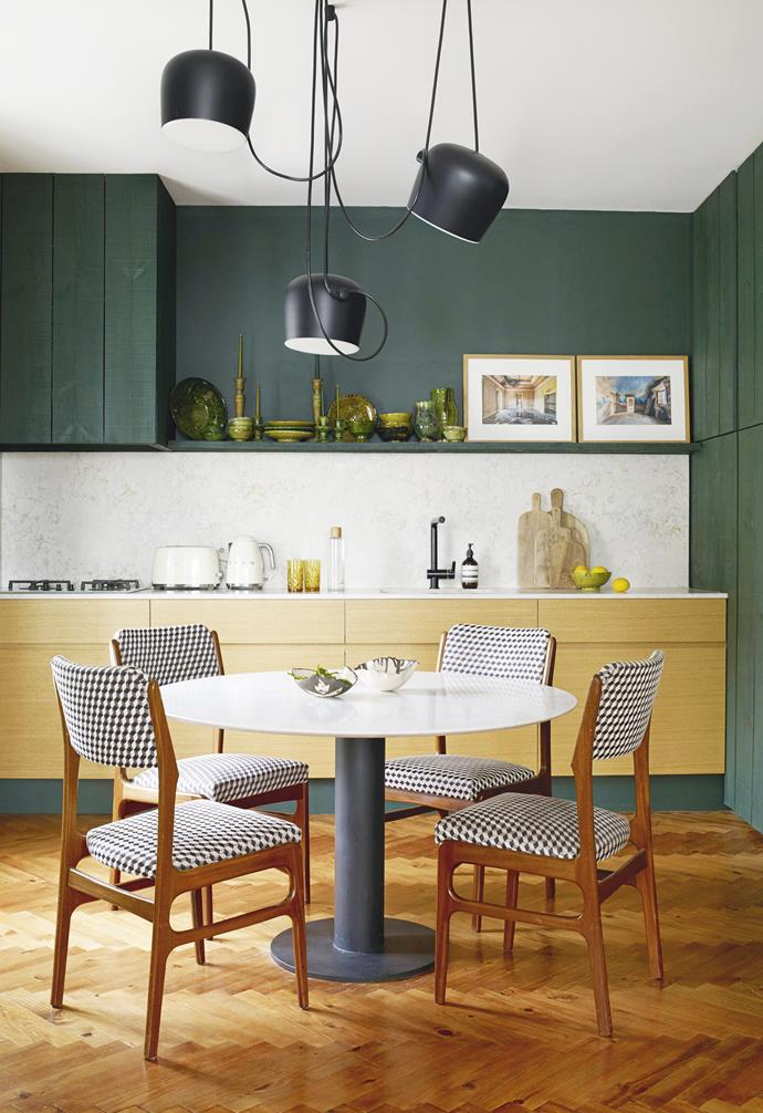 """**Kitchen** Olivier made the cabinets himself and used a self-mixed green paint. Smeg appliances complement the mix of old and new. A trio of 'Aim' pendant lights by Ronan & Erwan Bouroullec for Flos provides sculptural interest above the custom table. Olivier chose Silestone for the benchtop and splashback. Photographs (on shelf) by Aurelien Villette. Appliances, [Smeg](https://www.smeg.com.au/
