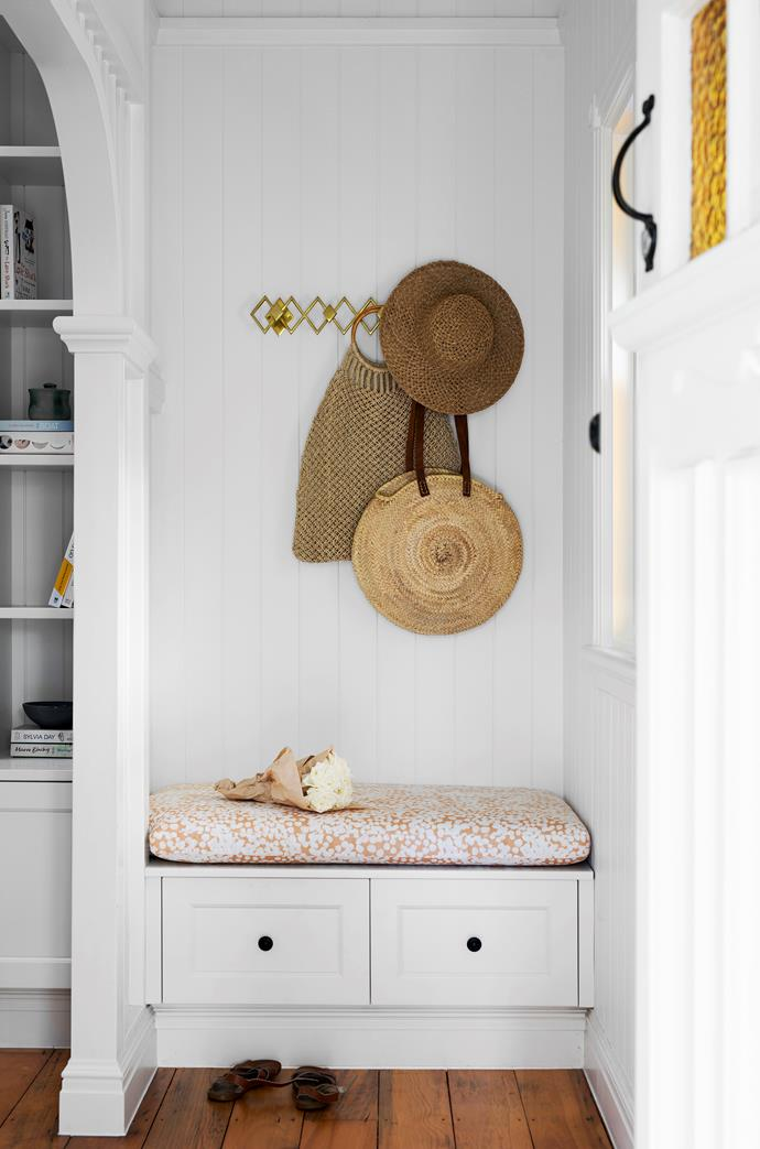 Opposite the front door on the first floor is a nook for coat, bag and shoe storage. The cabinetry is Polytec Ultra White. Stippled fabric (on built-in seat) from These Walls. 'Geo' multi hook with antiqued brass finish, $89, West Elm.