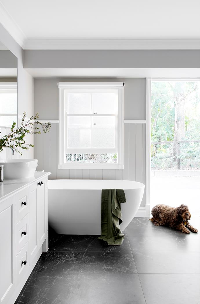 The bathroom is a family-friendly space where Murphy the mini labradoodle is also welcome. Bath and basin, Abey. Floor tiles, Burleigh Tiles. Towel, Nikau Store.