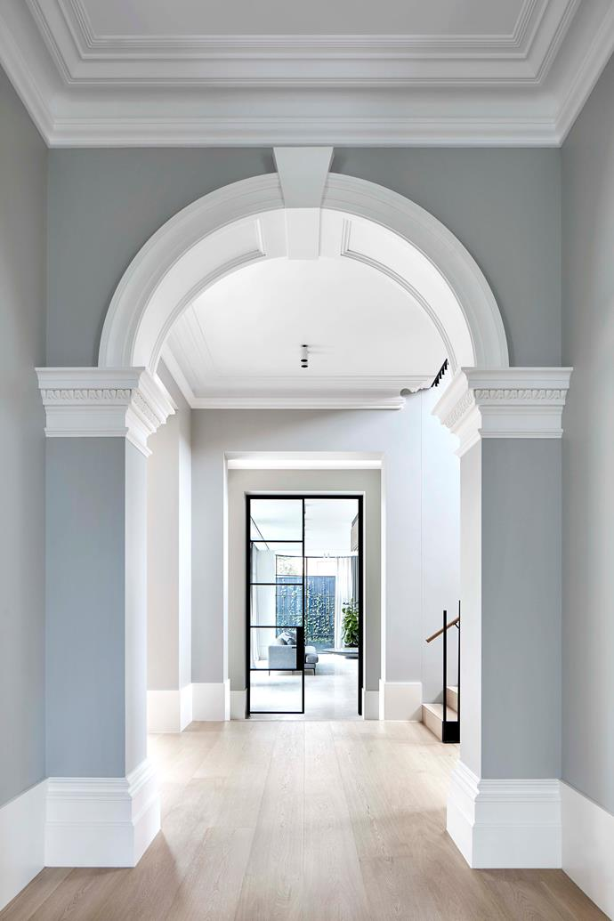 Christopher Elliott seamlessly combined the existing heritage features with an expansive new extension. In the hallway, the original Victorian arch leads to a glass steel door that opens onto the home's new addition.