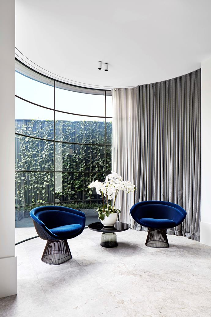 A black lacquer ClassiCon 'Bell' side table sits between a pair of Knoll 'Platner' chairs in blue velvet. The curved lines of the furniture echo the curved steel-framed window in this section of the living room.