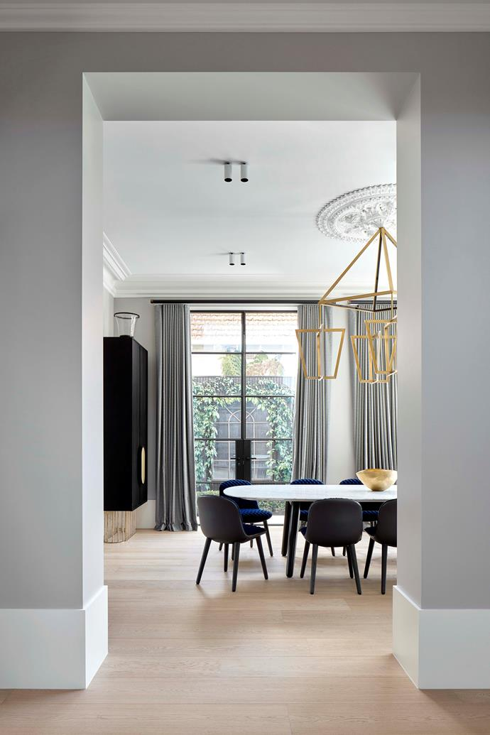 A contemporary brass pendant light hangs from a ceiling rose, signalling the home's blend of old and new. Custom wall unit and dining table by Christopher Elliott Design. 'Mad' dining chairs from Poliform.