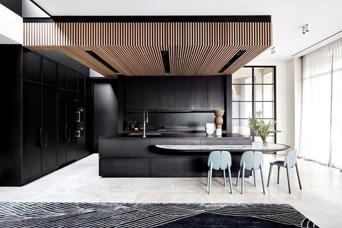 Timber slatting was introduced to add warmth to the black kitchen that the owner had requested. The slatting also helped to disguise the varying ceiling heights. The oval kitchen island bench with Arabescato marble top was added as there was no room for a separate dining table.