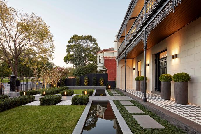 Symmetry in the front garden echoes the formal nature of the home's facade.
