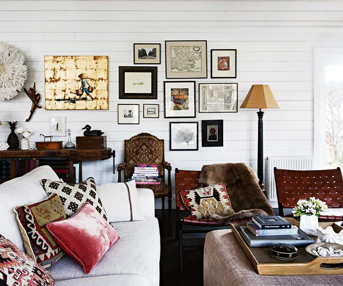 In the living room, an African headdress beside a painting by Sarah Bishop from Susie's hometown of Merriwa, and other art collected from around the world. The cushions were purchased in the UK, and the armchair from a former Bowral antiques shop.