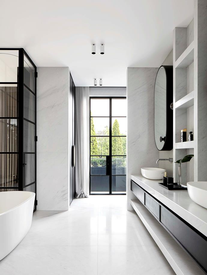 The hotel-inspired bathroom is lined with honed Bianco Carrara marble for a timeless look. Matt black finishes lend the space a modern, contemporary edge.
