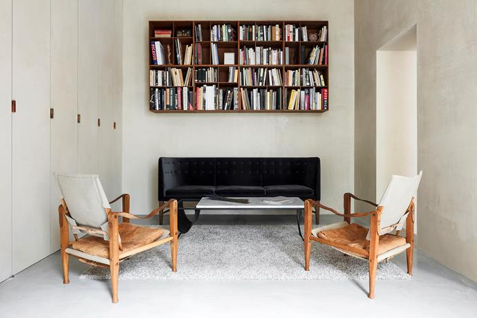 "In the living area, a pair of vintage safari chairs, a gift from Ask's father, provide contrast  yet sit in harmony with a velvet Arne Jacobsen & Flemming Lassen ""Mayor"" sofa, the couple's first furniture purchase."