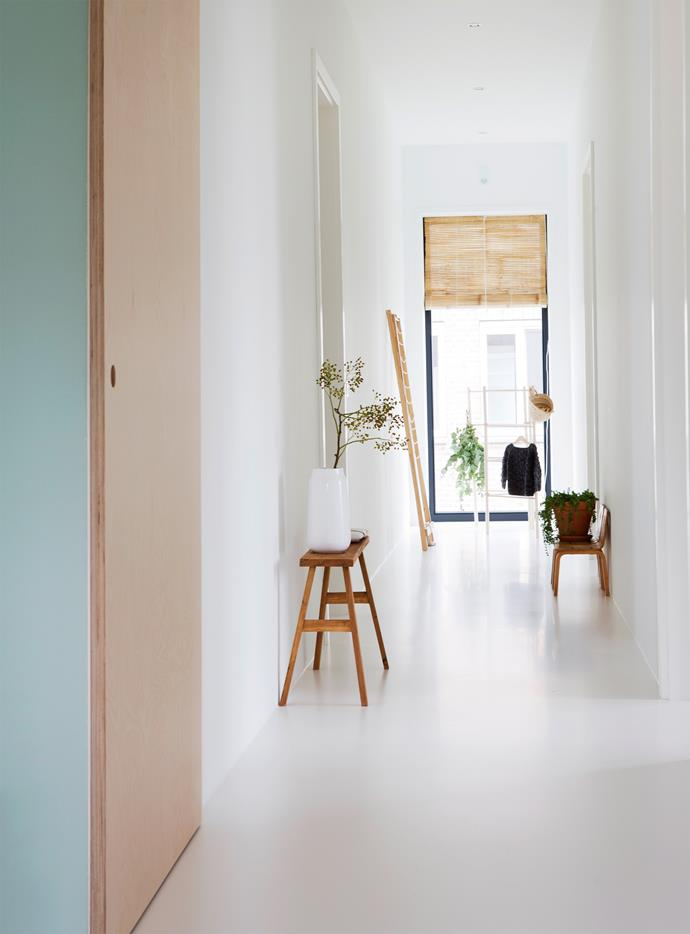 "The first floor features a white Béton Ciré (polished concrete and resin) floor, which gives the rooms a fresh and serene baseline for the family's understated [timber furniture and accessories](https://www.homestolove.com.au/scandi-style-furniture-6972|target=""_blank""). Heating and cooling is controlled by a water pump under the floor. ""By using this system, we don't need gas or fossil fuels,"" says Tessa. Sliding doors were also chosen for the rooms off the hallway to maximise space."