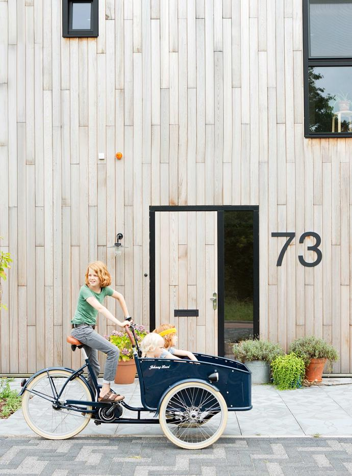 "Sustainably sourced wood used on the home's exterior and solar panels add to its eco credentials. ""We absolutely wanted a wooden house,"" says Tessa. ""Wood is a natural material and has a beautiful look and feel. The house is even insulated with wood fibre."" Mees, 11,  responsibly transports Polle, 8, and Guus, 5, on a super eco-friendly vehicle."