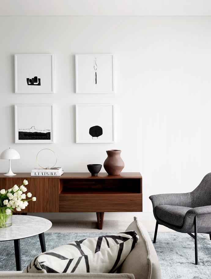 "A mid-century style timber console adds warmth to the contemporary living room. On the console is a 'Decoration Circle' by Kristina Dam Studio from [Designstuff](https://www.designstuff.com.au/kristina-dam-studio-decoration-circle/|target=""_blank""