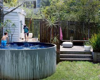 Two kids swimming in an above-ground concrete swimming pool.