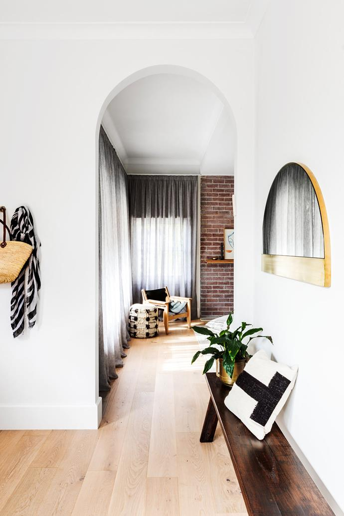 An arched mirror in the entrance echoes the new archway openings into the living room.