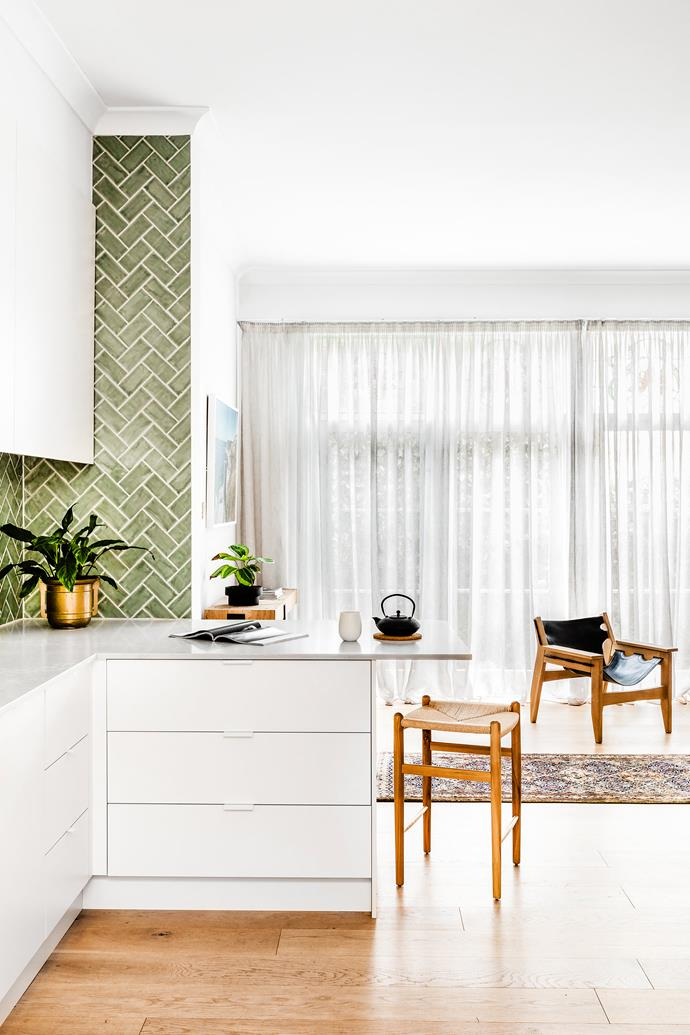 The kitchen features floating oak flooring and a large pantry. The green herringbone tiles work well the small space, creating visual interest.