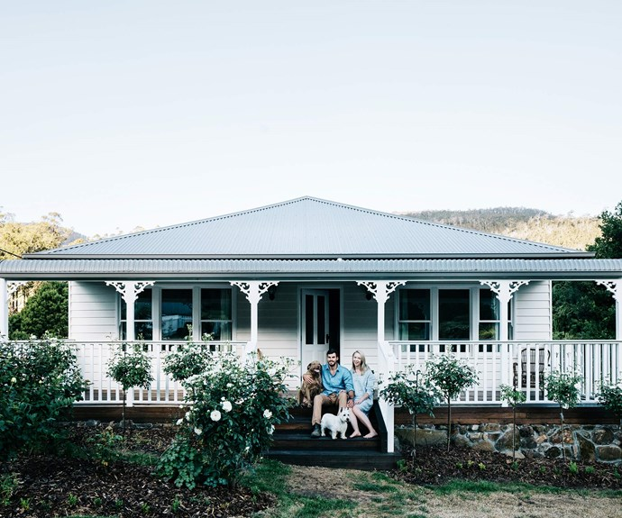 Laura and Boz on the front verandah of their century-old Crabtree Heights home, with their two dogs, Chesapeake Bay retriever Betty and West Highland terrier Ted. The couple planted standard roses out front to complement their home's storybook charm.| *Photography: Marnie Hawson*