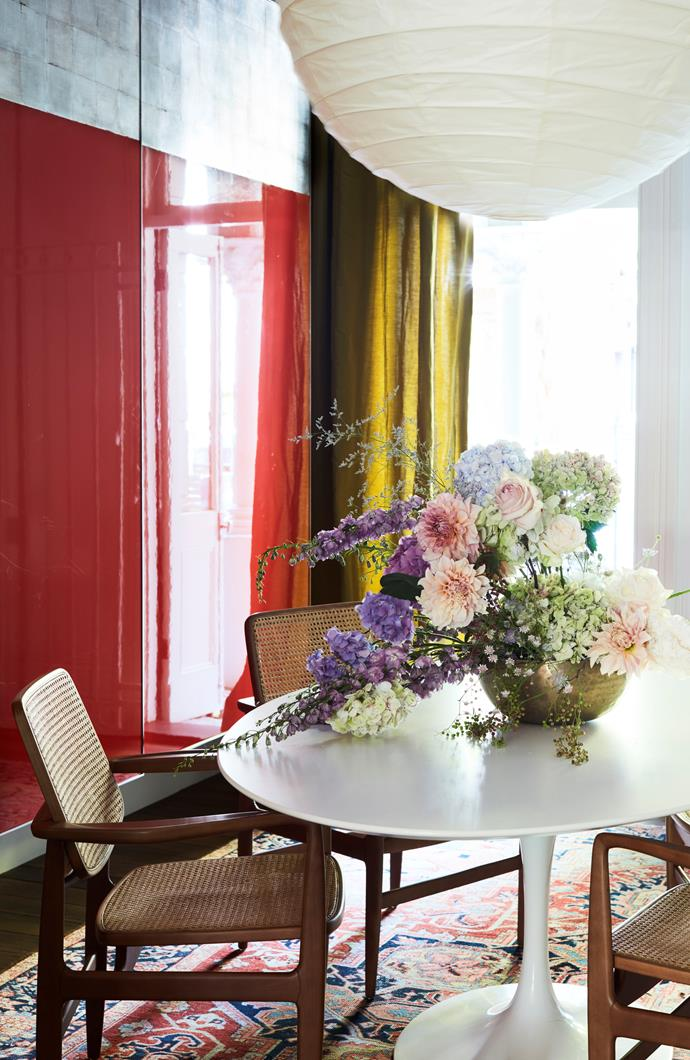 Knoll 'Saarinen' table with Brazilian chairs on a vintage Persian rug in the meeting room. Noguchi pendant light. Flowers by Grandiflora. Photograph by Prue Ruscoe.