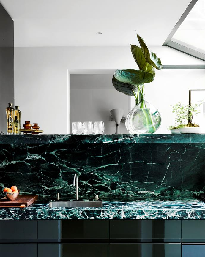 Emerald marble and dark green cabinetry in the kitchen.