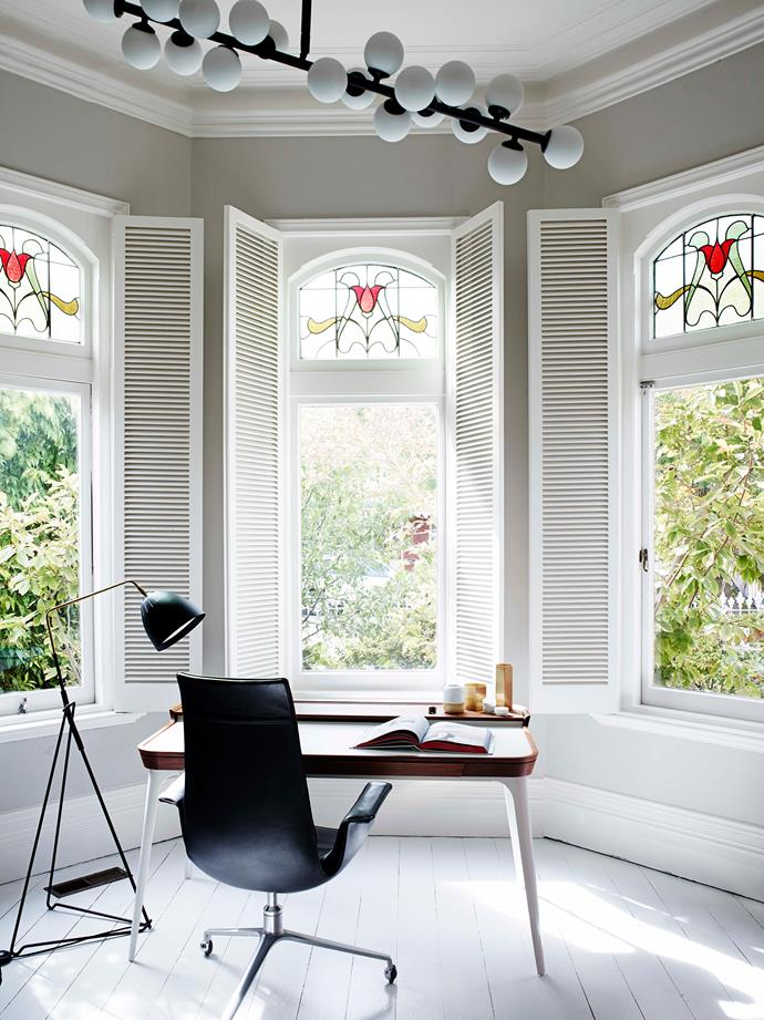A home office has been created by the original bay windows with leadlight glass. An Eames desk is paired with a vintage chair while a celestial pendant light adds a modern touch to the space.