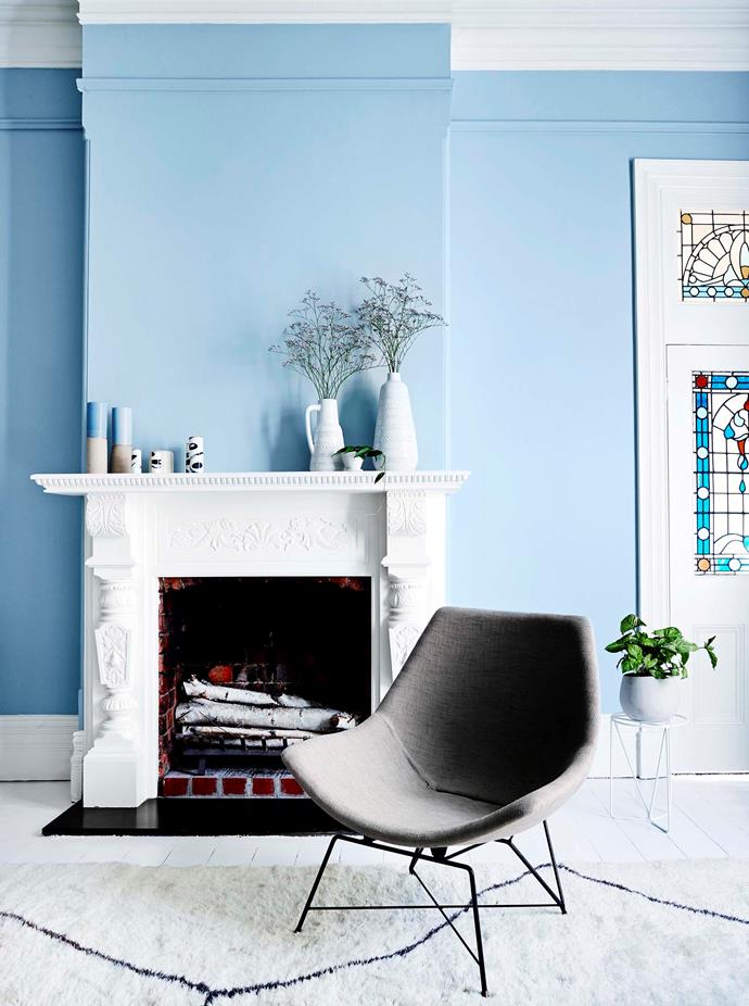 The crisp white fireplace mantle stands out against the cornflower blue wall in the living room.