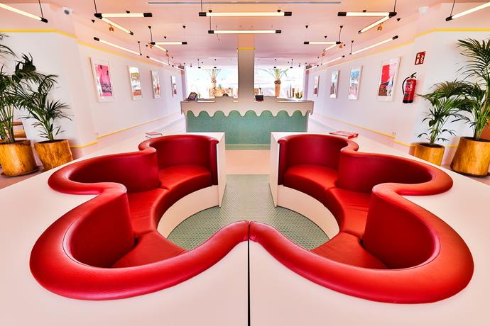 The hotel reception features a flower-shaped retro red lounge.