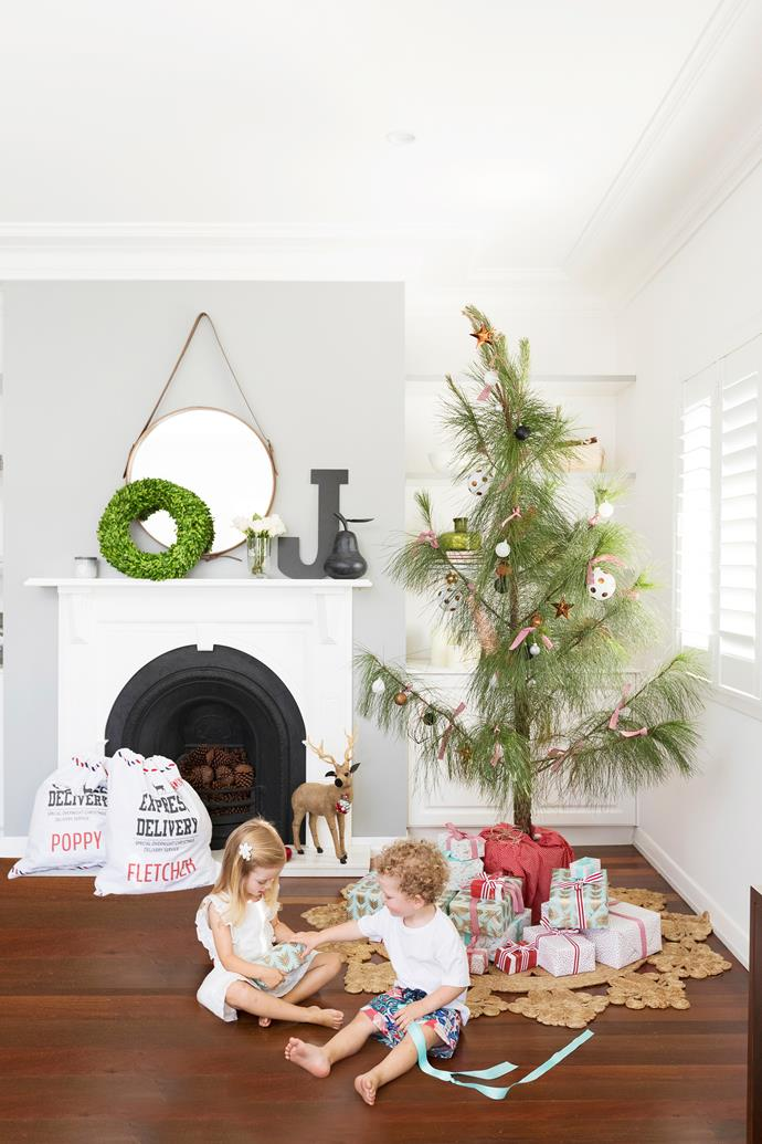"""The Christmas tree has been set up by he fireplace in the living room, """"Our handmade Christmas decorations with the kids' names are the first ones to go on the tree,"""" Holly says."""