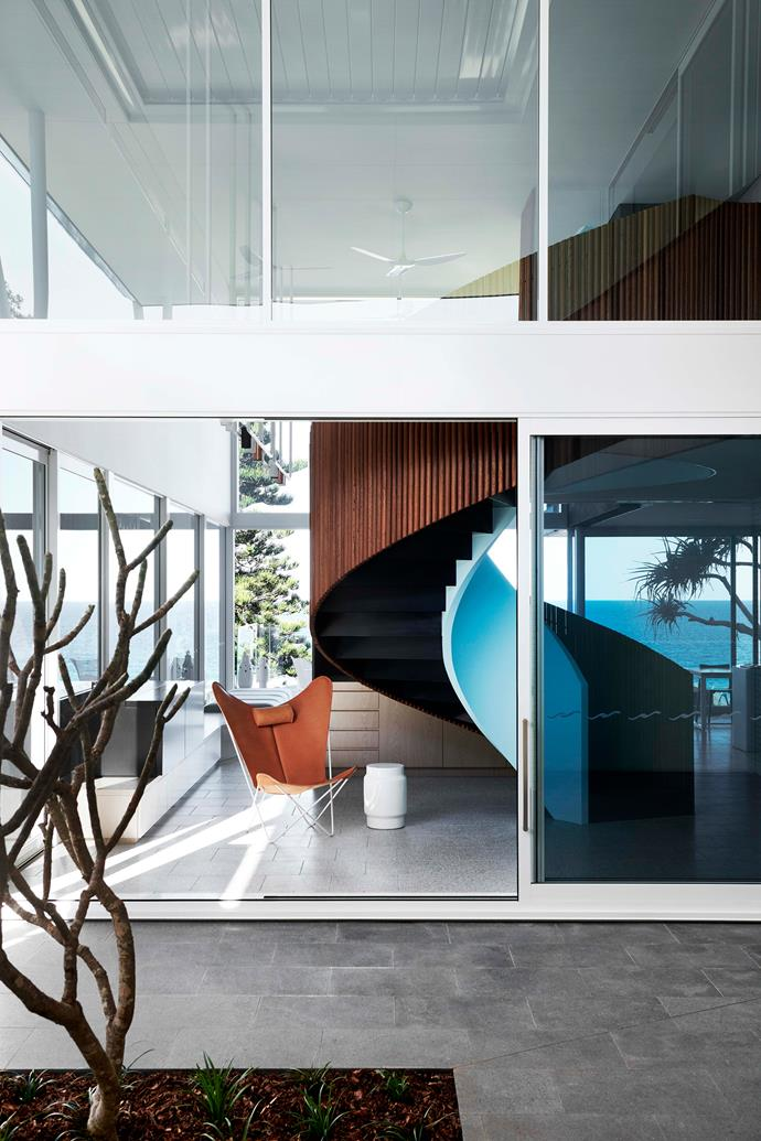 The line between the architecture and landscape is deliberately blurred. The home's upper level is in a dark, recessive tone intended to make it secondary when viewed from the beach to the garden's vegetation of local species of pandanus, banksia and dune plants.