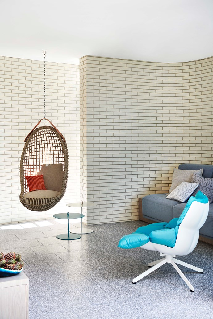 The corners of the living room are softened by the curving, exposed brick wall. B&B Italia 'Husk' armchair by Patricia Urquiola from Space, and Bonacina 1889 'Eureka' hanging chair from De De Ce. Bowl from Dinosaur Designs.