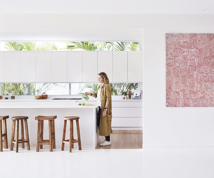 """**Kitchen and hallway** Emma in her airy kitchen, where glass windows do double duty as a splashback. In the hallway an artwork by Dick Ward adds a pop of colour at the entrance. Stools, [Bisque Interiors](https://bisqueinteriors.com.au/