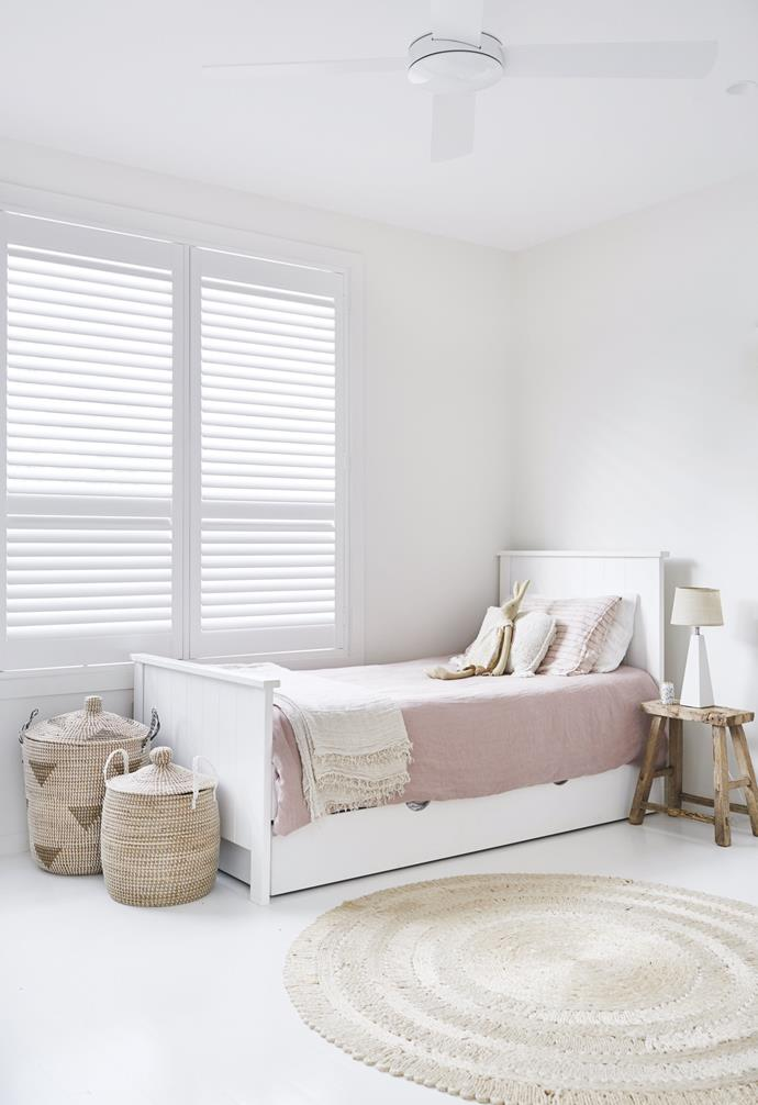 "**Girls' bedroom** Pastel pink bedlinen on the pull-out bed and the woven baskets and rug create a calm haven for the girls. Bedlinen, [Cultiver](https://cultiver.com.au/|target=""_blank""