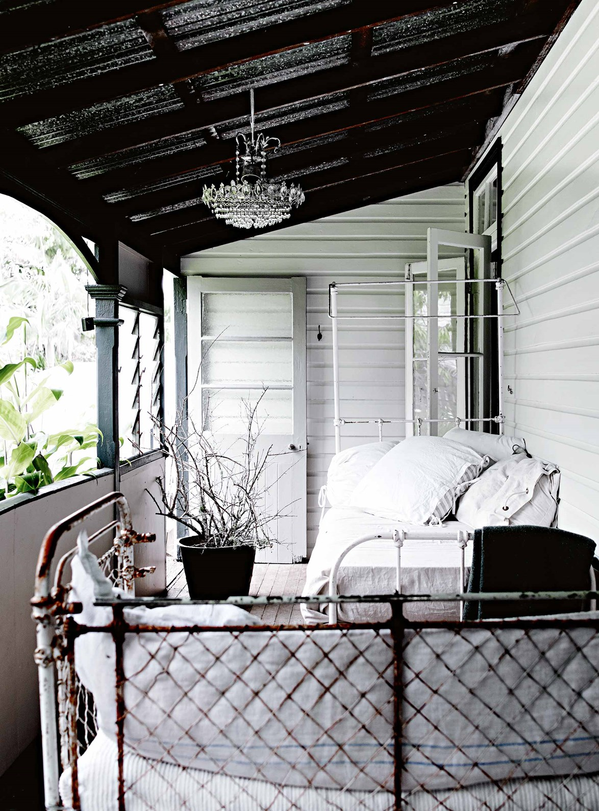 "Comfy vintage daybeds and a sparkling chandelier have transformed an old verandah into a shabby chic retreat. That's because the verandah is where [Byron Bay homeowner and dressmaker](https://www.homestolove.com.au/dressmakers-white-vintage-interior-in-the-byron-bay-hinterland-13719|target=""_blank"") Michelle Douglas does the majority of her work, designing and sewing clothing for her two labels [Meg By Design](https://megbydesign.com/