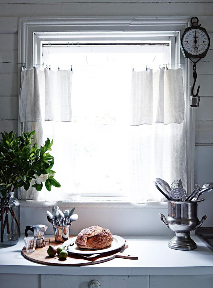 Handmade curtains line the double-hung windows in the kitchen.