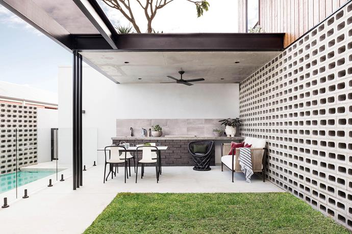 Concrete breeze blocks, Brikmakers. Custom concrete benchtops. Exposed steelwork painted Dulux Satin Black. Vitra 'Belleville' outdoor dining setting, Living Edge. *Photo:* Dion Robeson