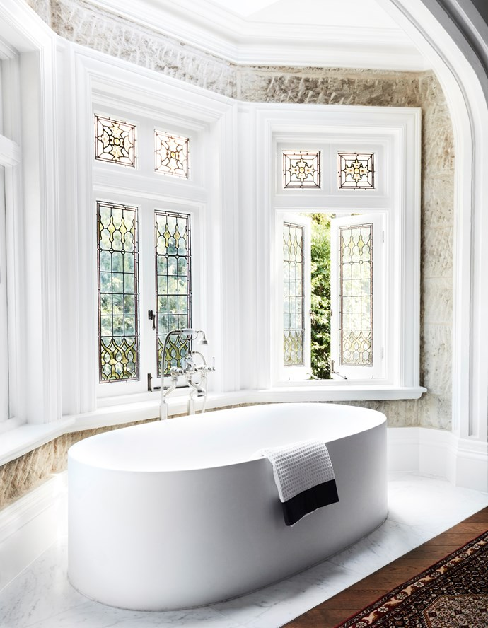 """The minimal Boffi bathtub in the ensuite of this [Sydney home by Hancock Architects](https://www.homestolove.com.au/gothic-revival-home-19307 target=""""_blank"""") sits in front of a wall of convict-worked sandstone and stained-glass windows. *Photograph*: Prue Ruscoe *Styling*: Alexandra Gordon. From *Belle* November 2018."""