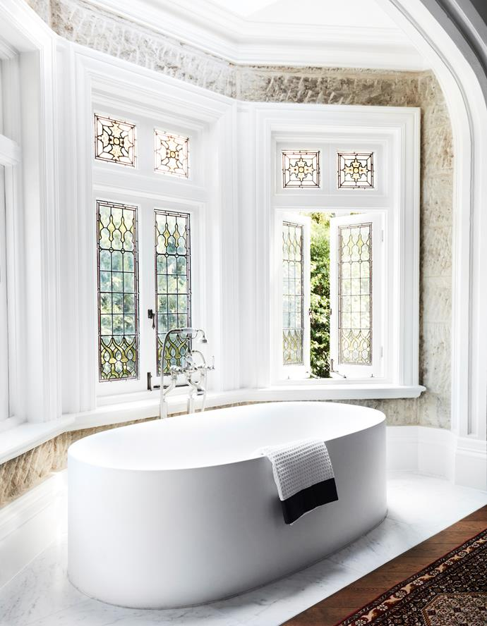 "The minimal Boffi bathtub in the ensuite of this [Sydney home by Hancock Architects](https://www.homestolove.com.au/gothic-revival-home-19307|target=""_blank"") sits in front of a wall of convict-worked sandstone and stained-glass windows. *Photograph*: Prue Ruscoe *Styling*: Alexandra Gordon. From *Belle* November 2018."