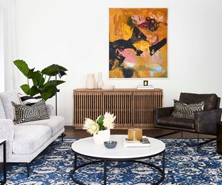 Living room with blue oriental rug and orange artwork