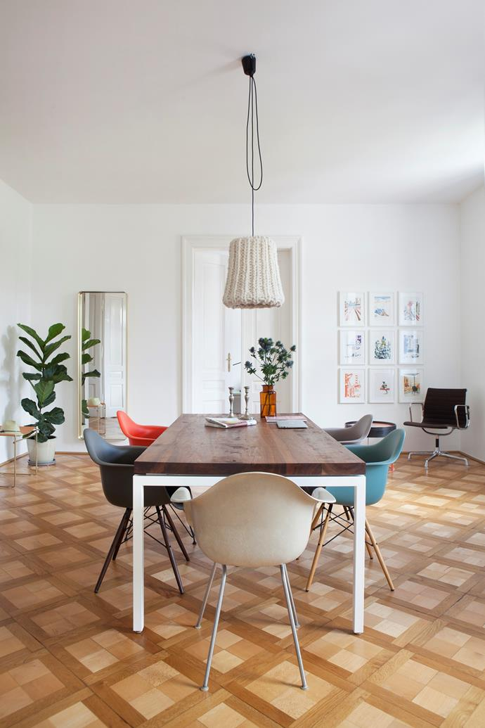 Nina made the walnut-topped dining table as a present for her partner Karsten. Colourful Eames armchairs surround it. The Granny pendant lamp is by Nina's former design studio Pudelskern.