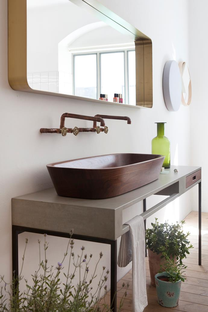 "[Plants in the bathroom](https://www.homestolove.com.au/plants-suitable-for-bathrooms-1755|target=""_blank"") create a spa-like feel. The double Shell basin, a seamless bowl carved from walnut, sits on a concrete table with its integrated towel rail and walnut drawer."