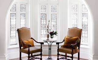 Two antique armchairs in front of a lead light bay window