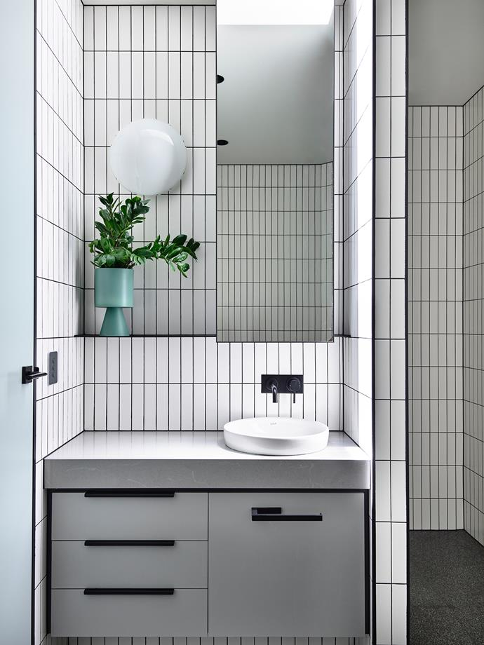 In the family bathroom, white tiles with black grouting was used an inexpensive way to create pattern. The matt-white vanity top is Quantum Quartz 'Pietra Serena' reconstituted stone. Wall tiles, Signorino.