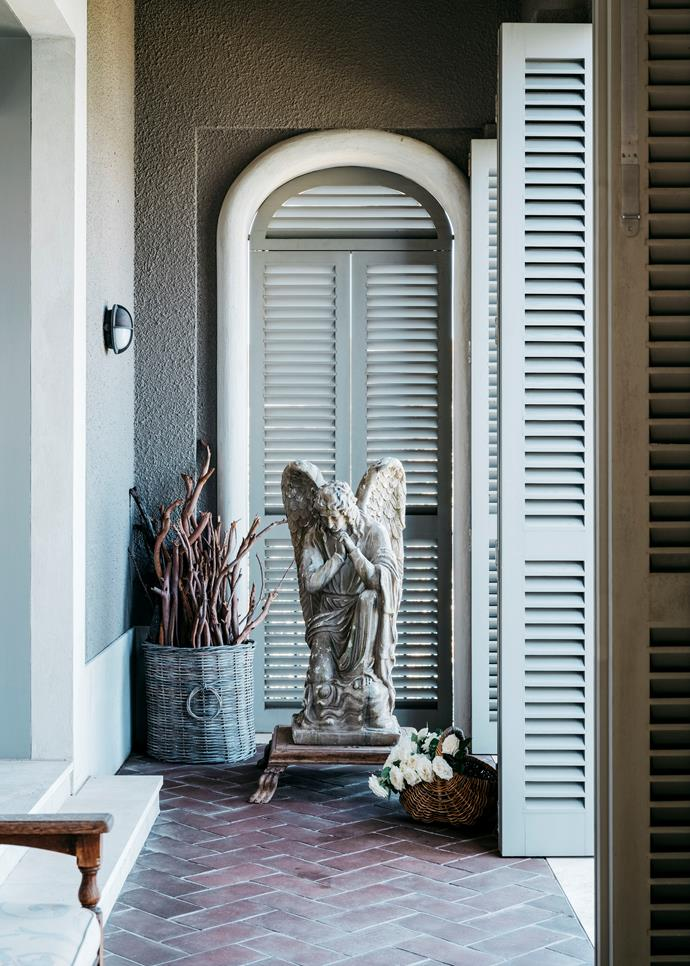 Kindling is stored in an antique basket off the living room. Shutters handmade by Woodhill Joinery. Custom sage paint by Rikki Stubbs from Pure Colour.