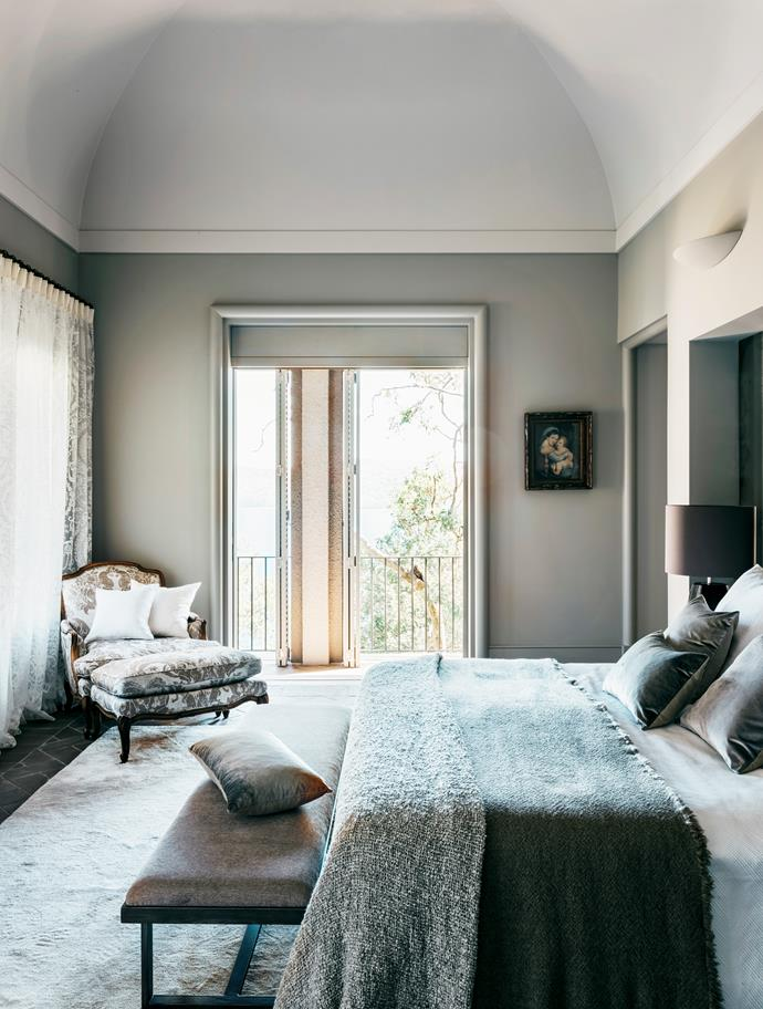 In the main bedroom, Iosis velvet cushions in grey and Harmony linen cushions in white from Francalia. Society Limonta throw and 'Des' blanket from Ondene. Old Italian crystoleum painting of Madonna and child.