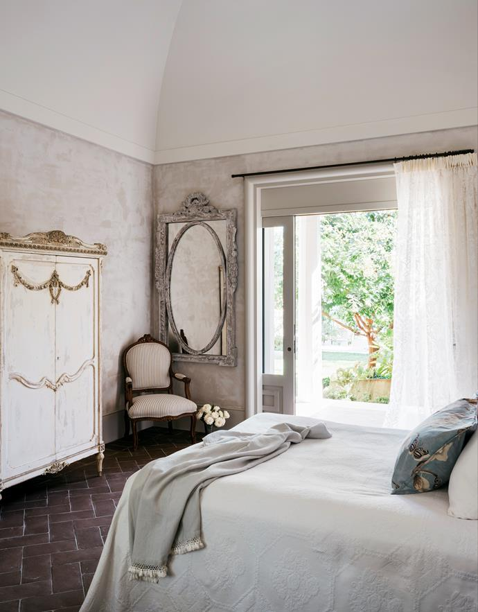 In a guestroom, French antique armoire and wall mirror bought in the UK. Vintage Marcella quilt and throw.