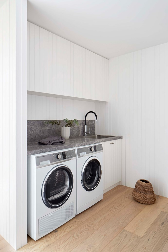 In the laundry, a Fisher & Paykel washer and heat-pump dryer are tucked under a limestone bench.