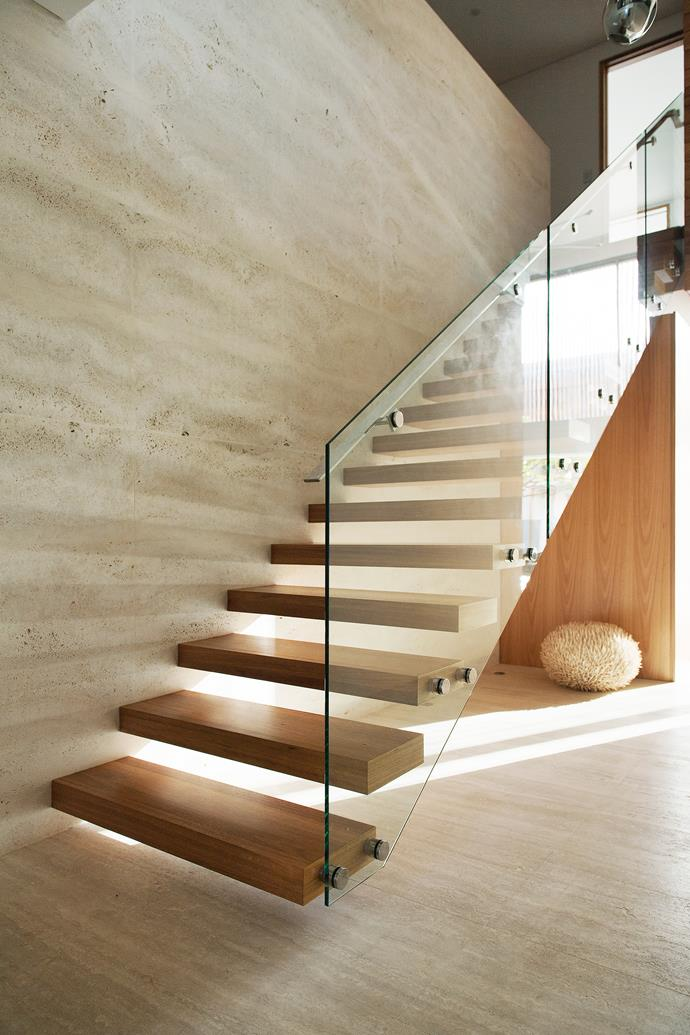"""The steps are cantilevered blackbutt with a glass-and-steel balustrade. Raw travertine tiles create a feature wall. """"They are the same tiles as on the floor but unfilled so you can really appreciate the texture,"""" says Chevonne."""