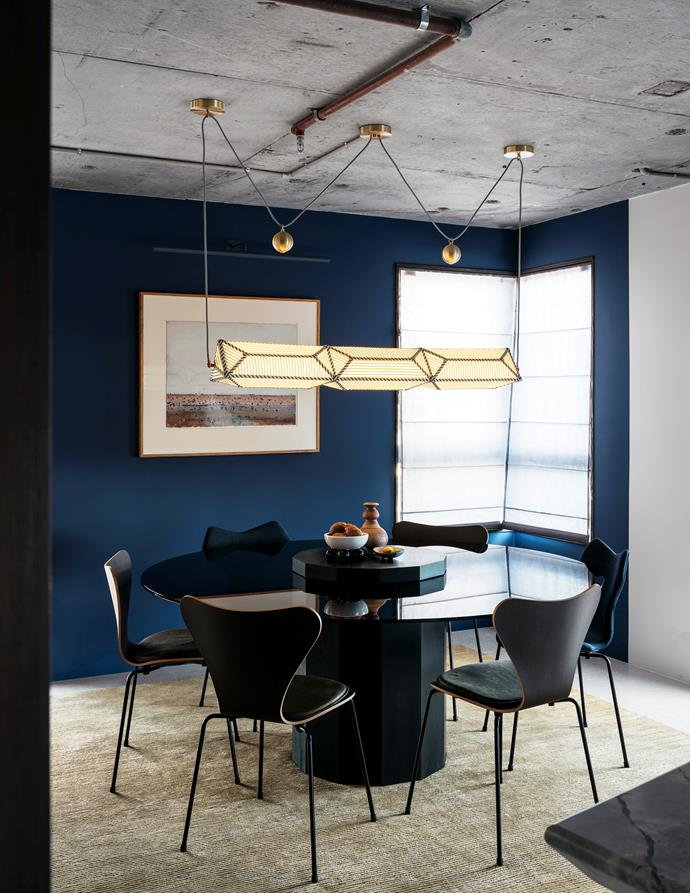 Custom 'Apollo 1906' table designed by Amber Road and made by Jonathan West with 'Series 7' and upholstered 'Grand Prix' chairs from Cult beneath a 'Hyperlink' pendant light by Erich Ginder.
